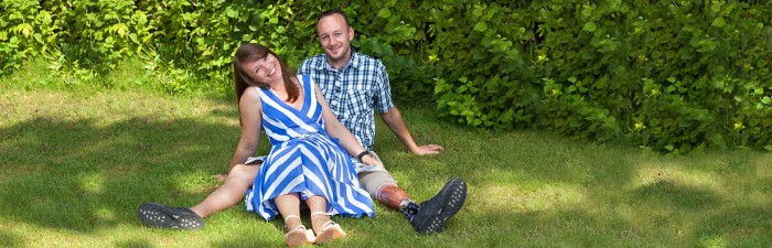Happy couple sat on the grass